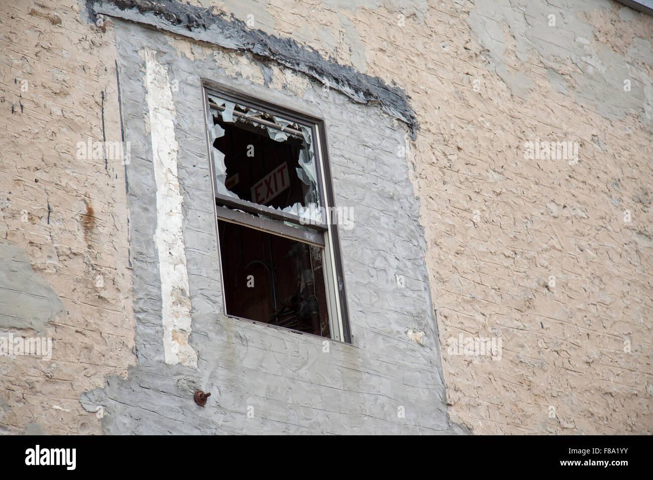 broken window on stone building vandalism - Stock Image