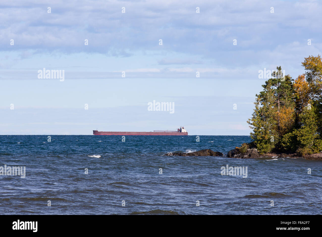 Great Lakes oar boat on the horizon passing behind a rocky island with trees.  Low hanging clouds and plenty of - Stock Image