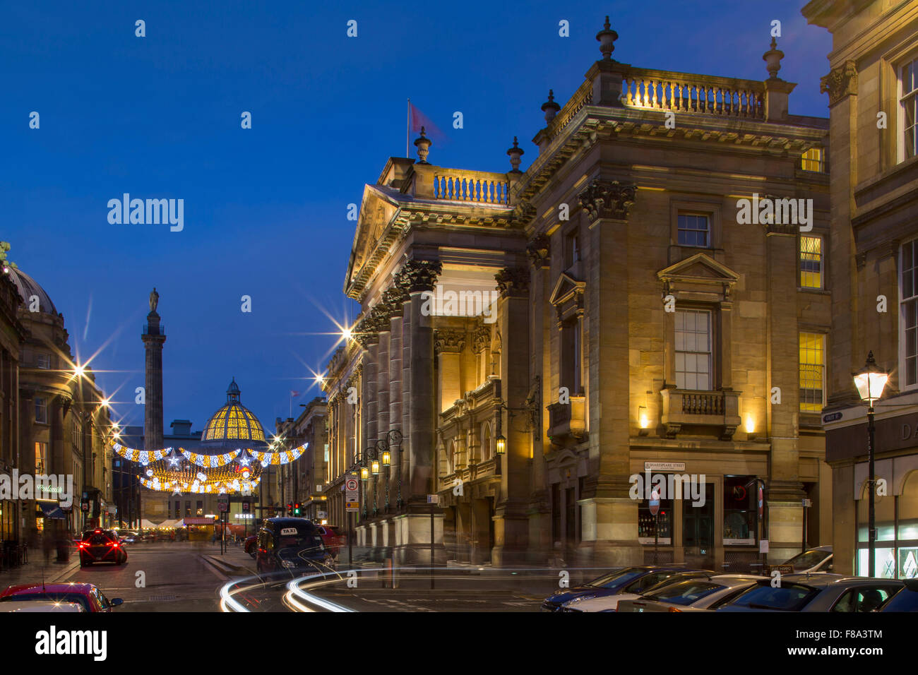An external view of The Theatre Royal in Newcastle upon Tyne at dusk at Christmas looking towards Grey's Monument - Stock Image