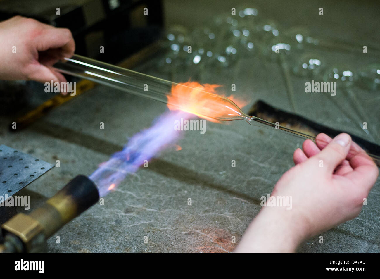 Piotrkow Trybunalski, Poland. 7th December, 2015. Worker heats piece of glass in order to form a glass ball at 'Szkło - Stock Image