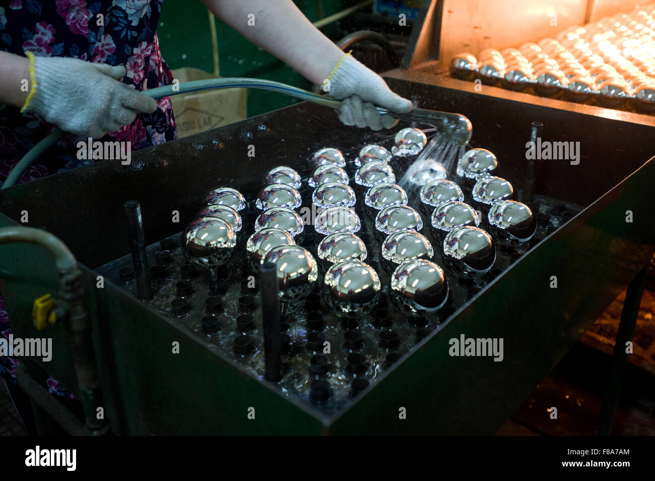 Piotrkow Trybunalski, Poland. 7th December, 2015. Worker washes silvered glass balls before placing them into drying - Stock Image