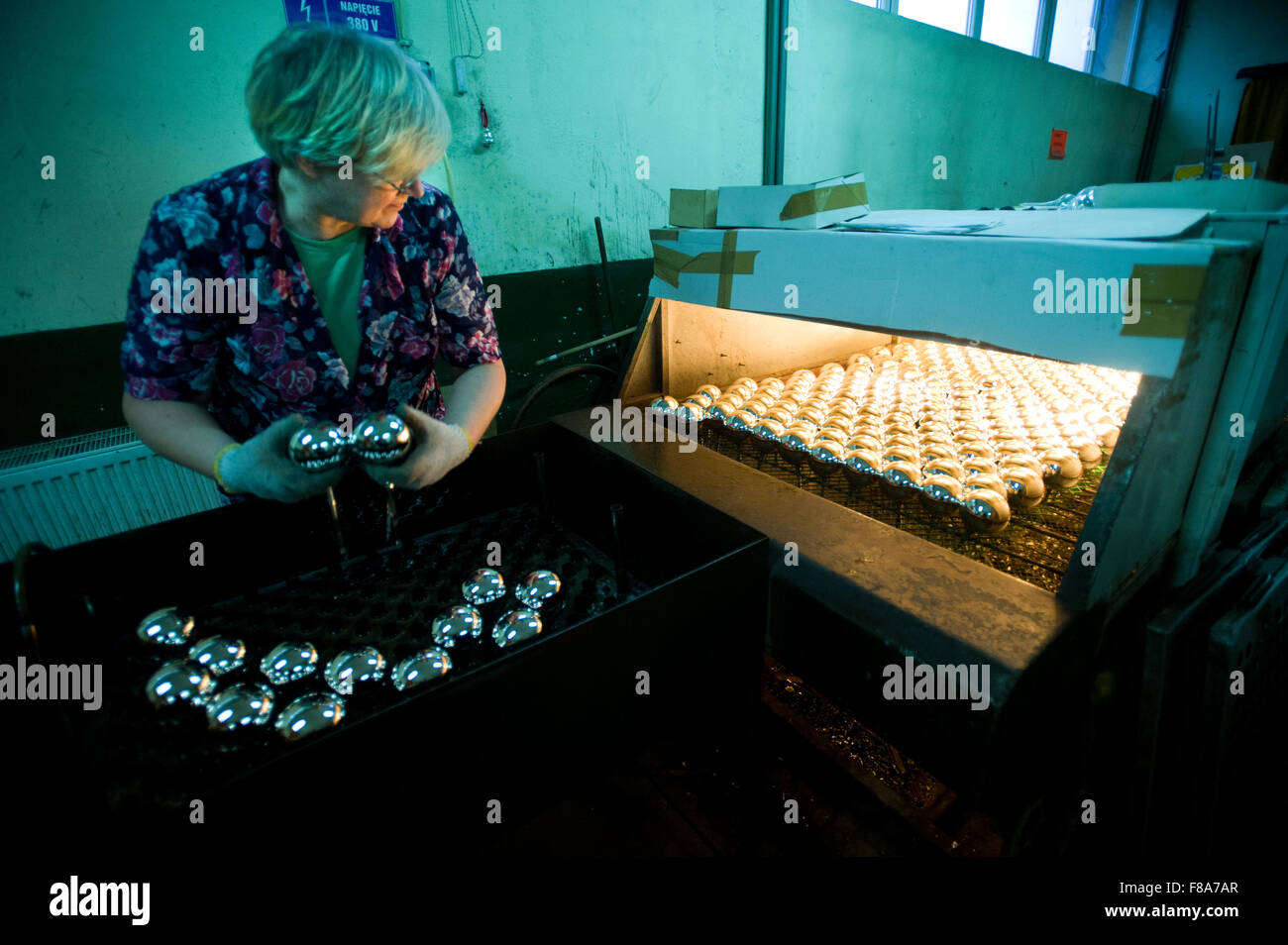 Piotrkow Trybunalski, Poland. 7th December, 2015. Worker places silvered glass balls into drying machine at 'Szkło - Stock Image