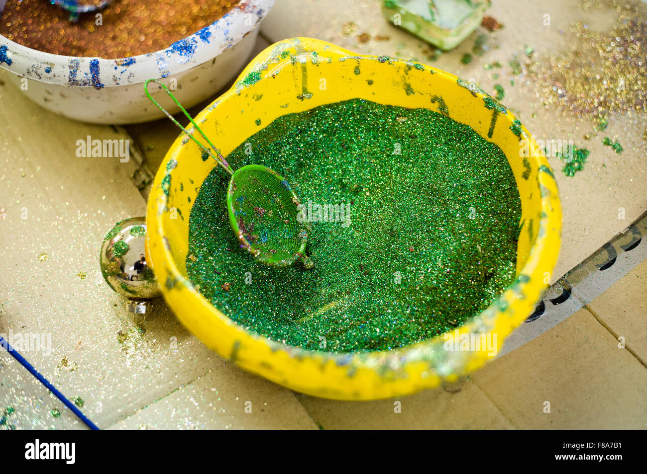 Piotrkow Trybunalski, Poland. 7th December, 2015. Yellow plastic bowl filled with green glitter used to ornament - Stock Image