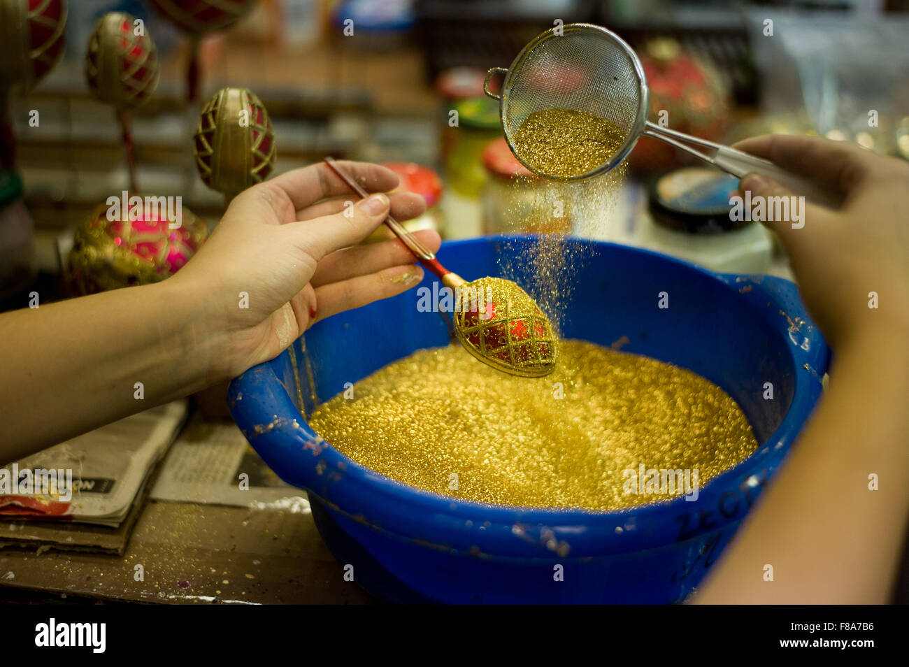 Piotrkow Trybunalski, Poland. 7th December, 2015. Worker decorates Christmas ball with golden glitter  at 'Szkło - Stock Image