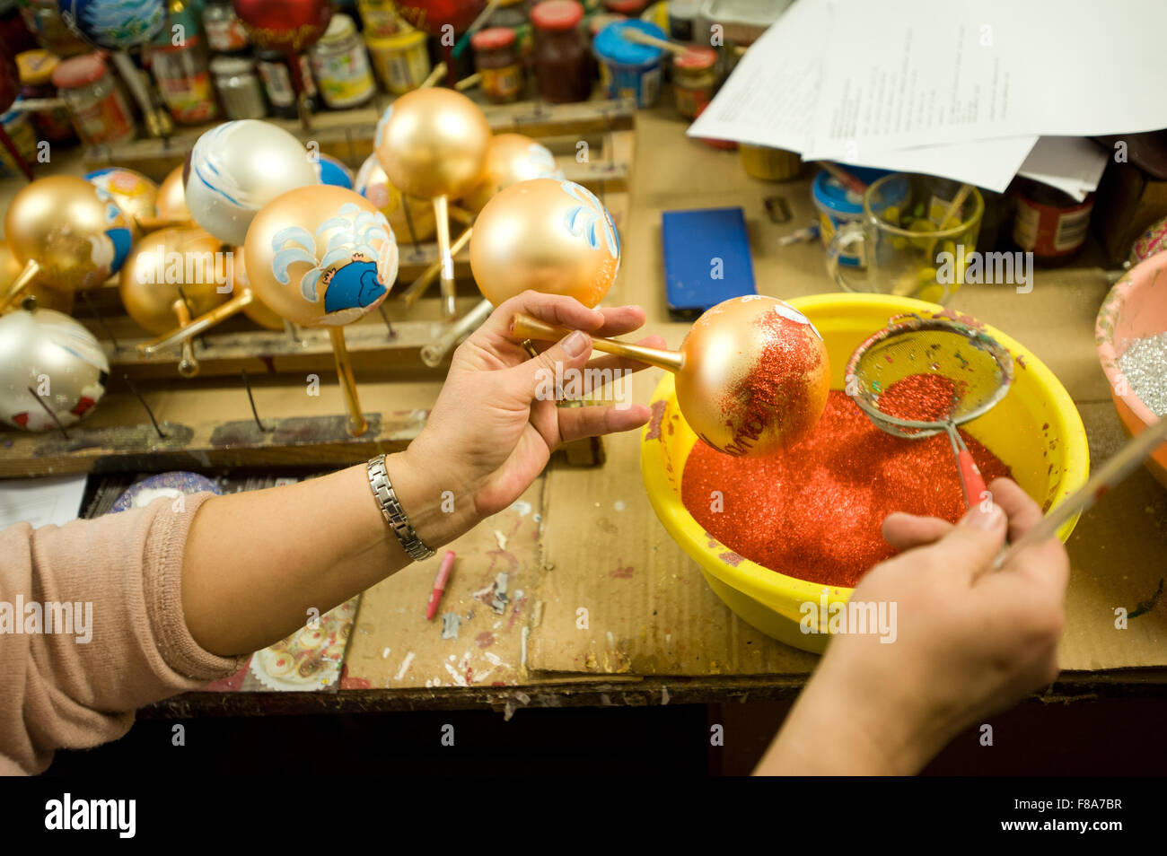 Piotrkow Trybunalski, Poland. 7th December, 2015. Worker decorates christmas ball with red glitter at 'Szkło - Stock Image