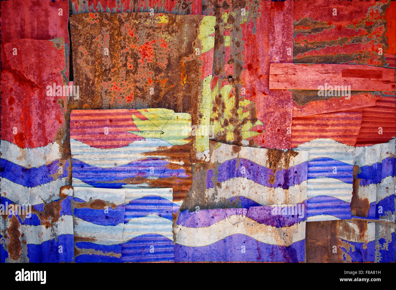 An abstract background image of the flag of Kiribati painted on to rusty corrugated iron sheets overlapping to form - Stock Image