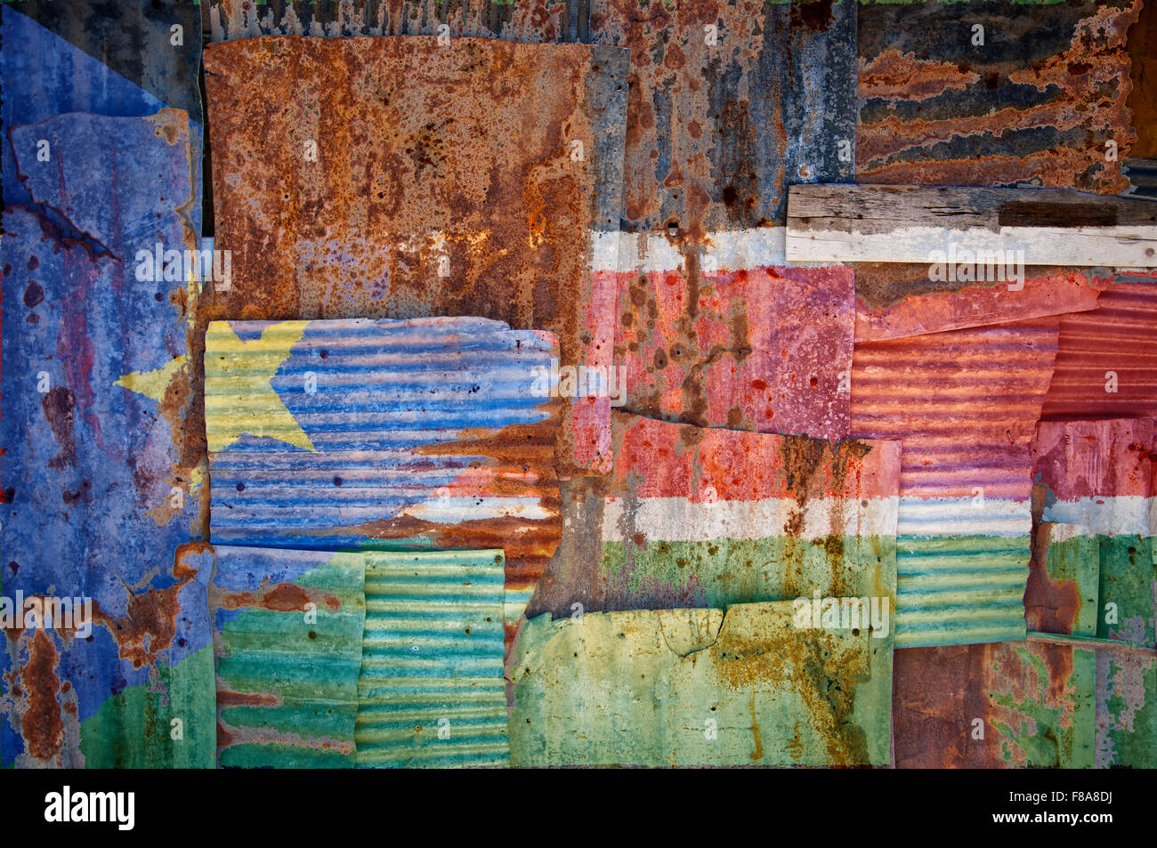 An abstract background image of the flag of South Sudan painted on to rusty corrugated iron sheets overlapping to - Stock Image