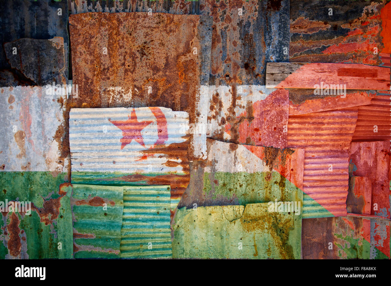 An abstract background image of the flag of Western Sahara painted on to rusty corrugated iron sheets overlapping - Stock Image