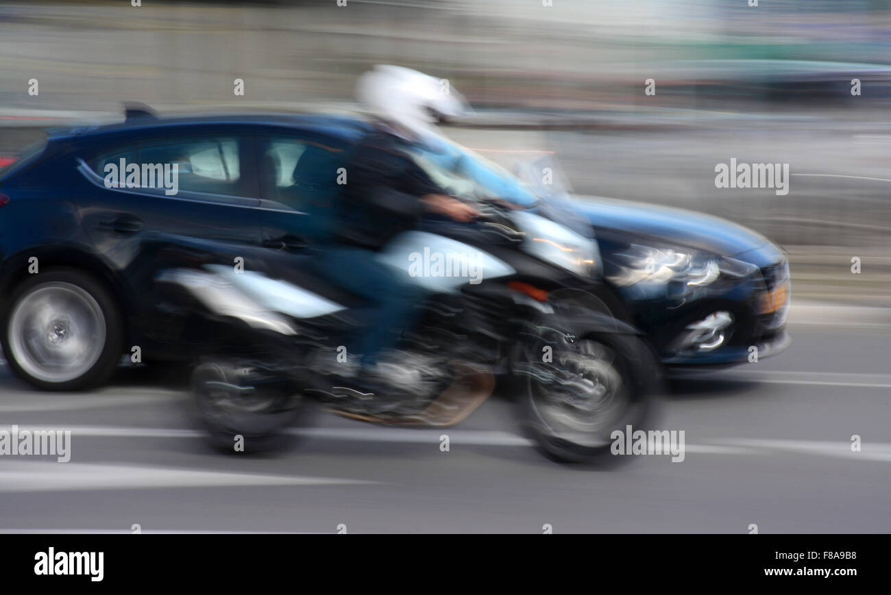 Car and motorbike in blurred motion - Stock Image