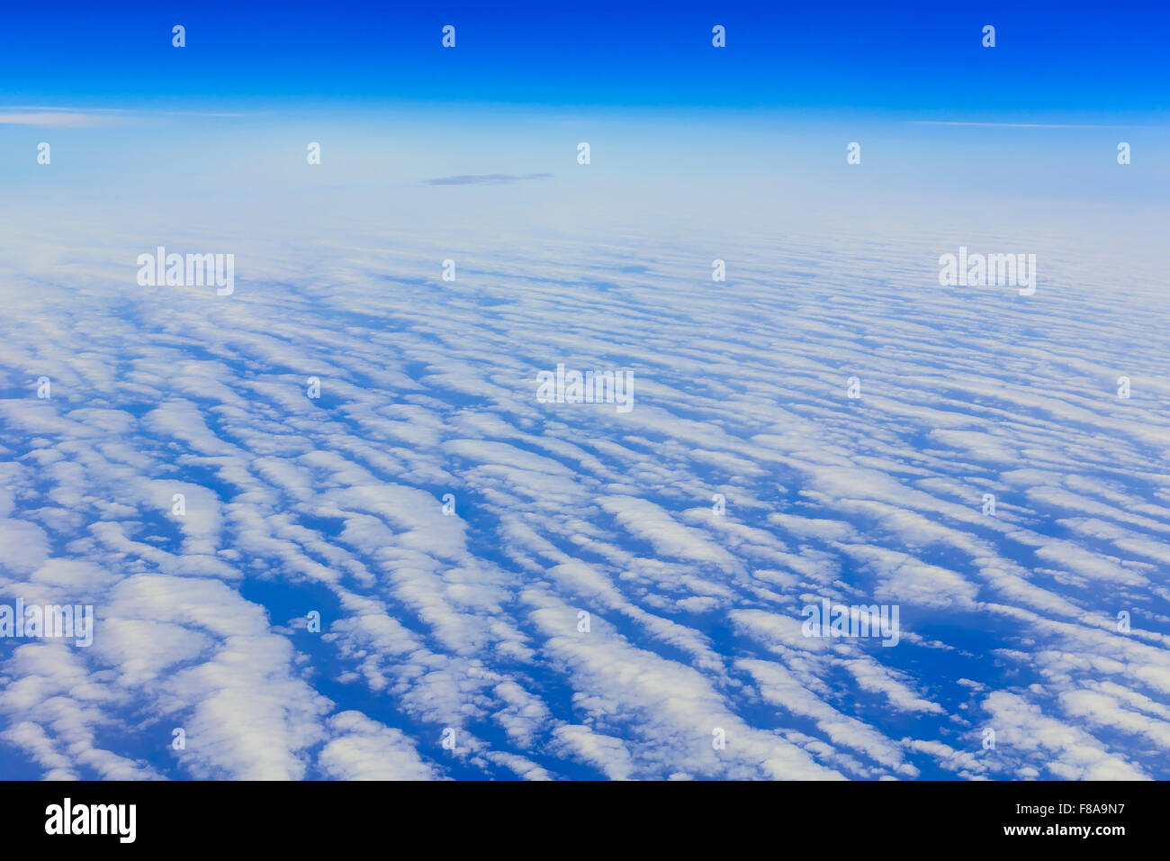 View on blue sky above white clouds from the window of airplane with skyline over ocean Stock Photo