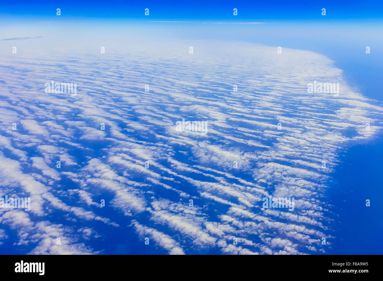 View on blue sky above white clouds from the window of airplane with skyline above ocean Stock Photo