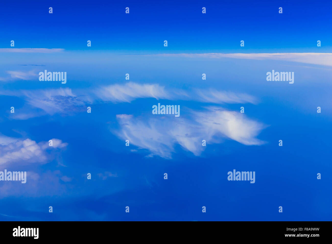 View on blue sky above white clouds from the window of plane with horizon above ocean Stock Photo