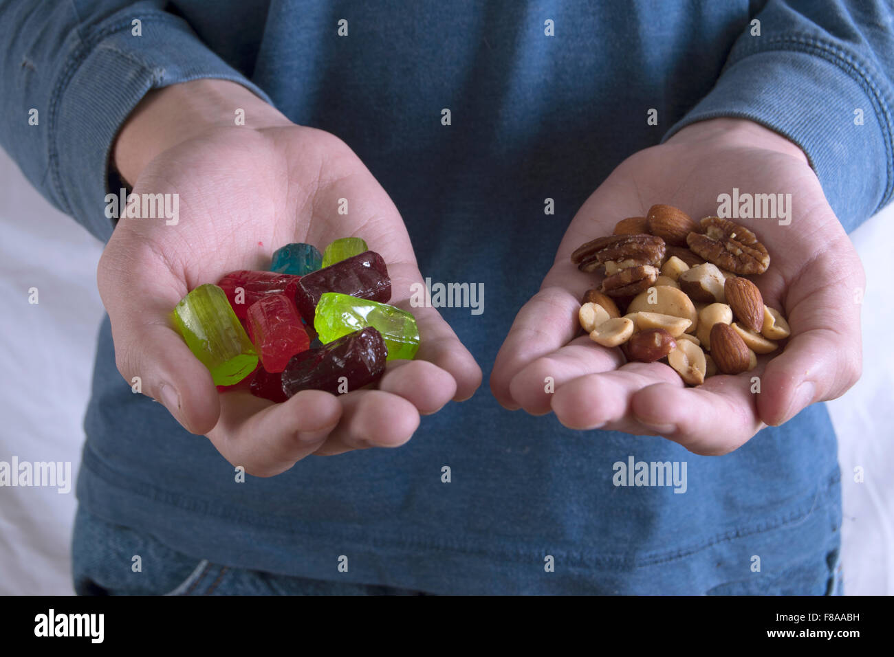 healthy and junk food in hands - Stock Image