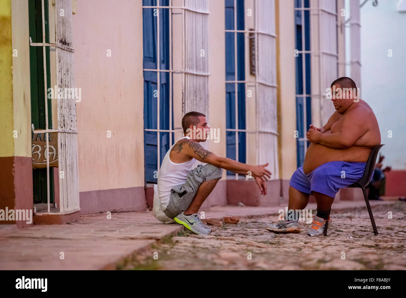Street scene with an overweight Cubans in Trinidad, Street Scene, Cuba at the blue hour, Trinidad, Cuba, Sancti - Stock Image