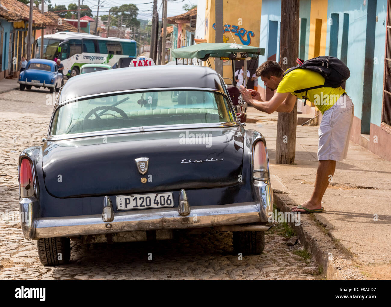 Tourist photographed in a vintage car on the roadside in the old town of Trinidad, Street Scene, Trinidad, pavement, - Stock Image