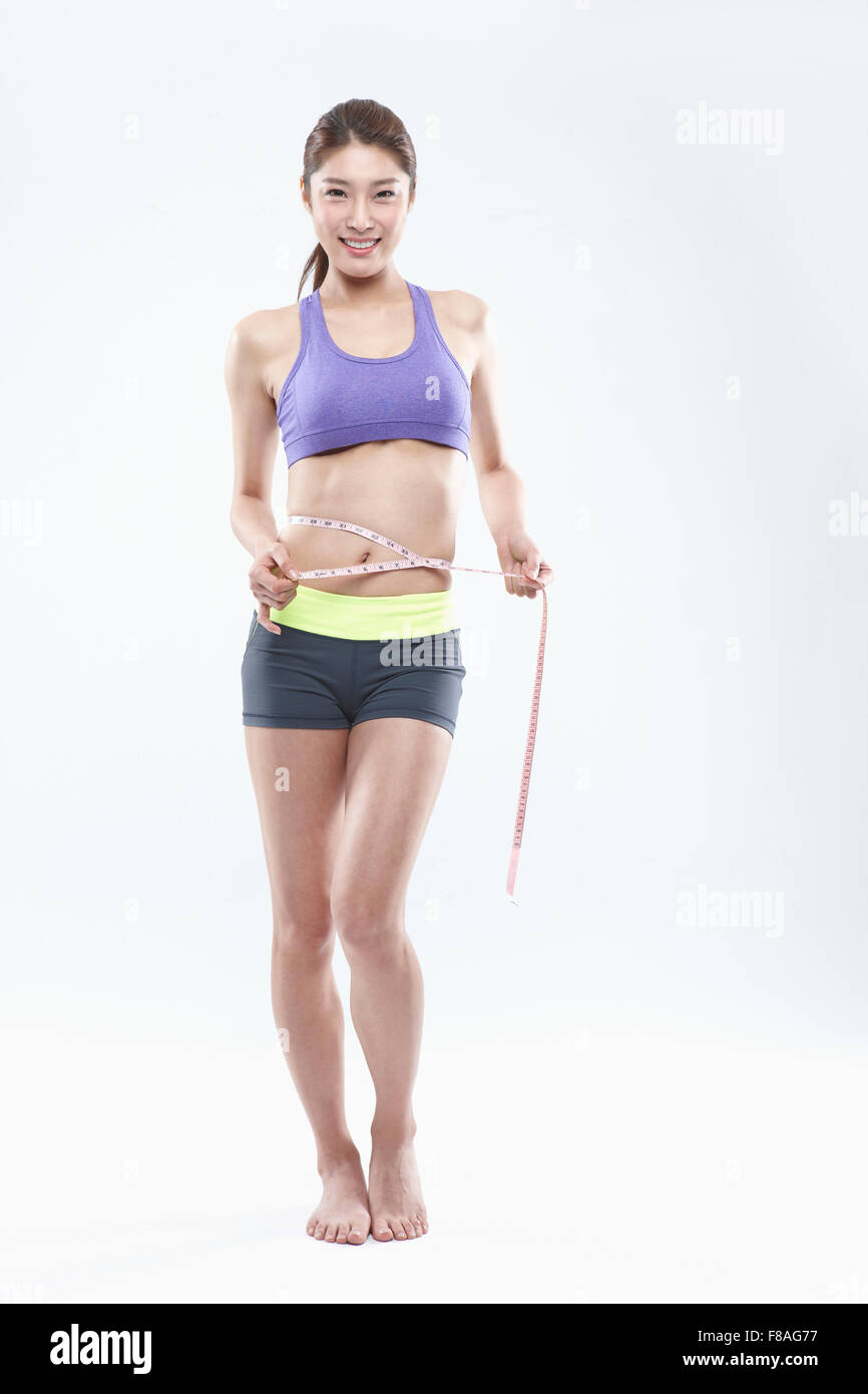 Standing woman in sportswear with a tapeline around her waist Stock Photo