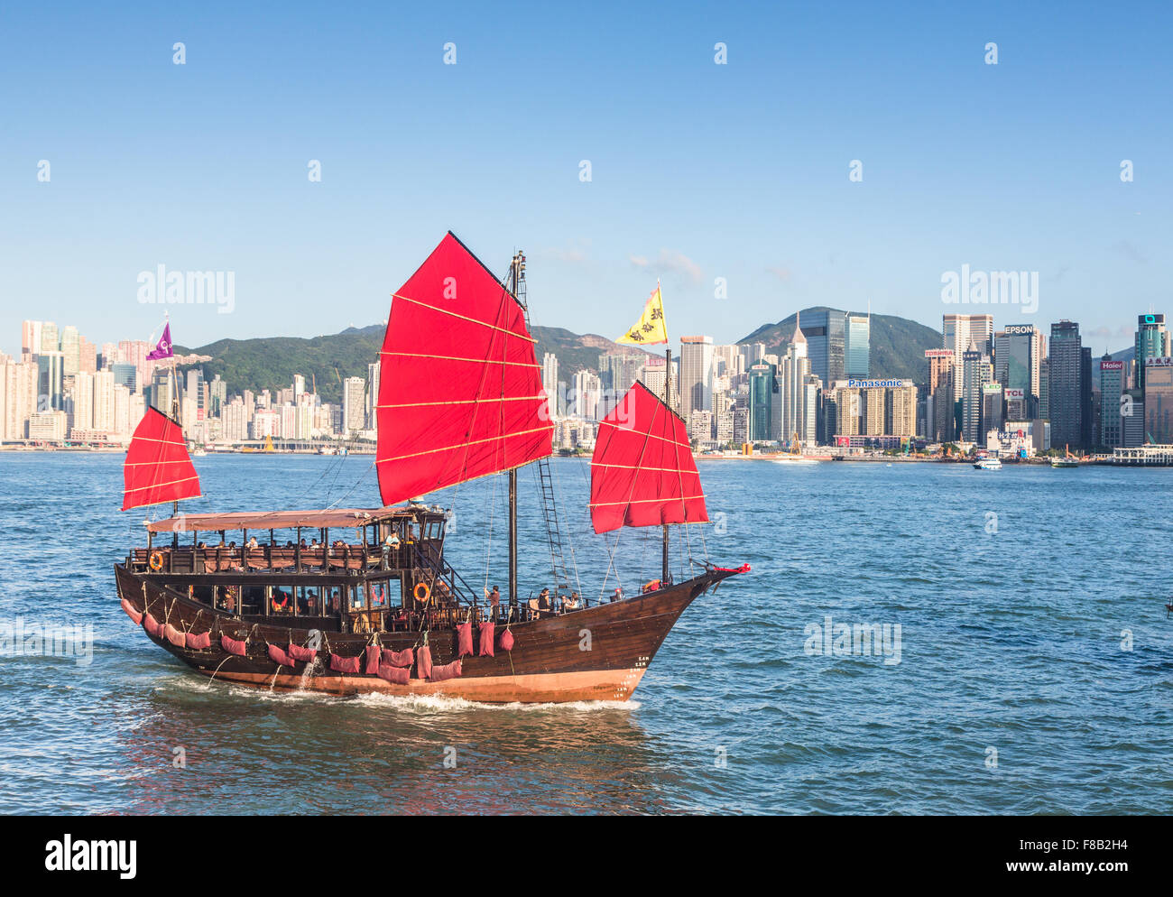A tourist boat, build as a traditional Chinese junk, sails in Victoria harbor in Hong Kong - Stock Image