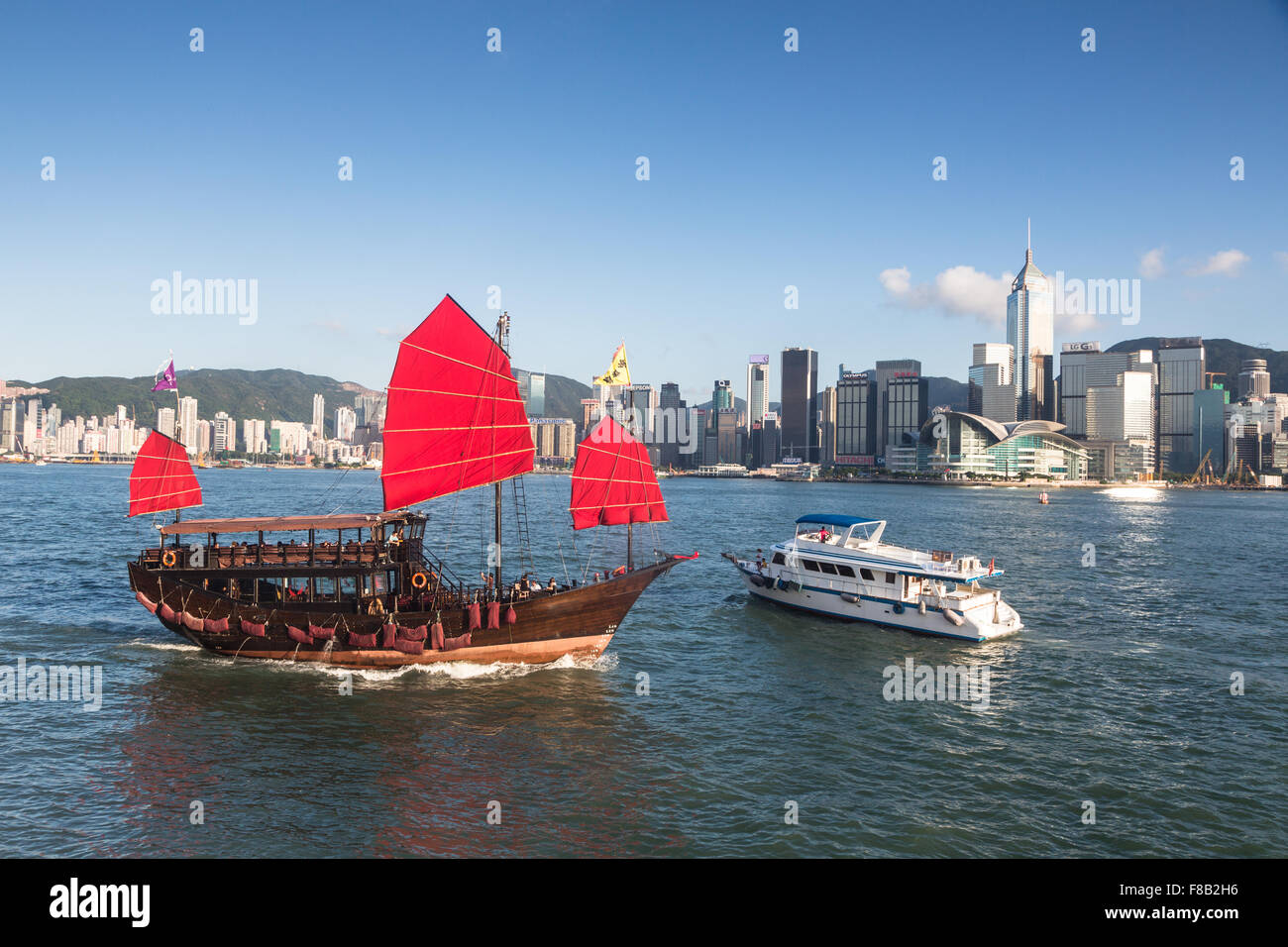 A tourist junk crosses a modern boat in Victoria harbor in Hong Kong - Stock Image