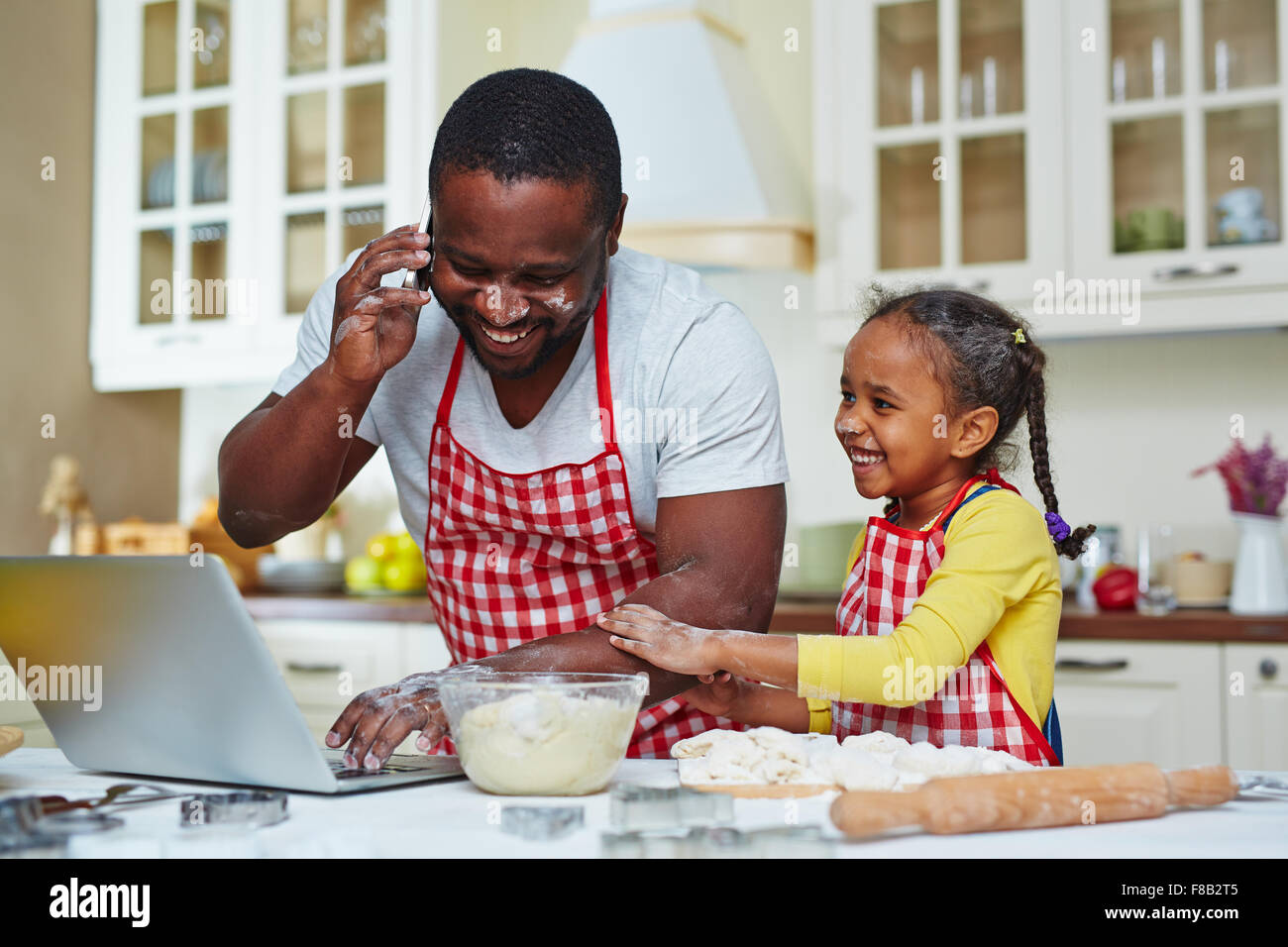 Young man calling and networking in the kitchen with his daughter near by - Stock Image