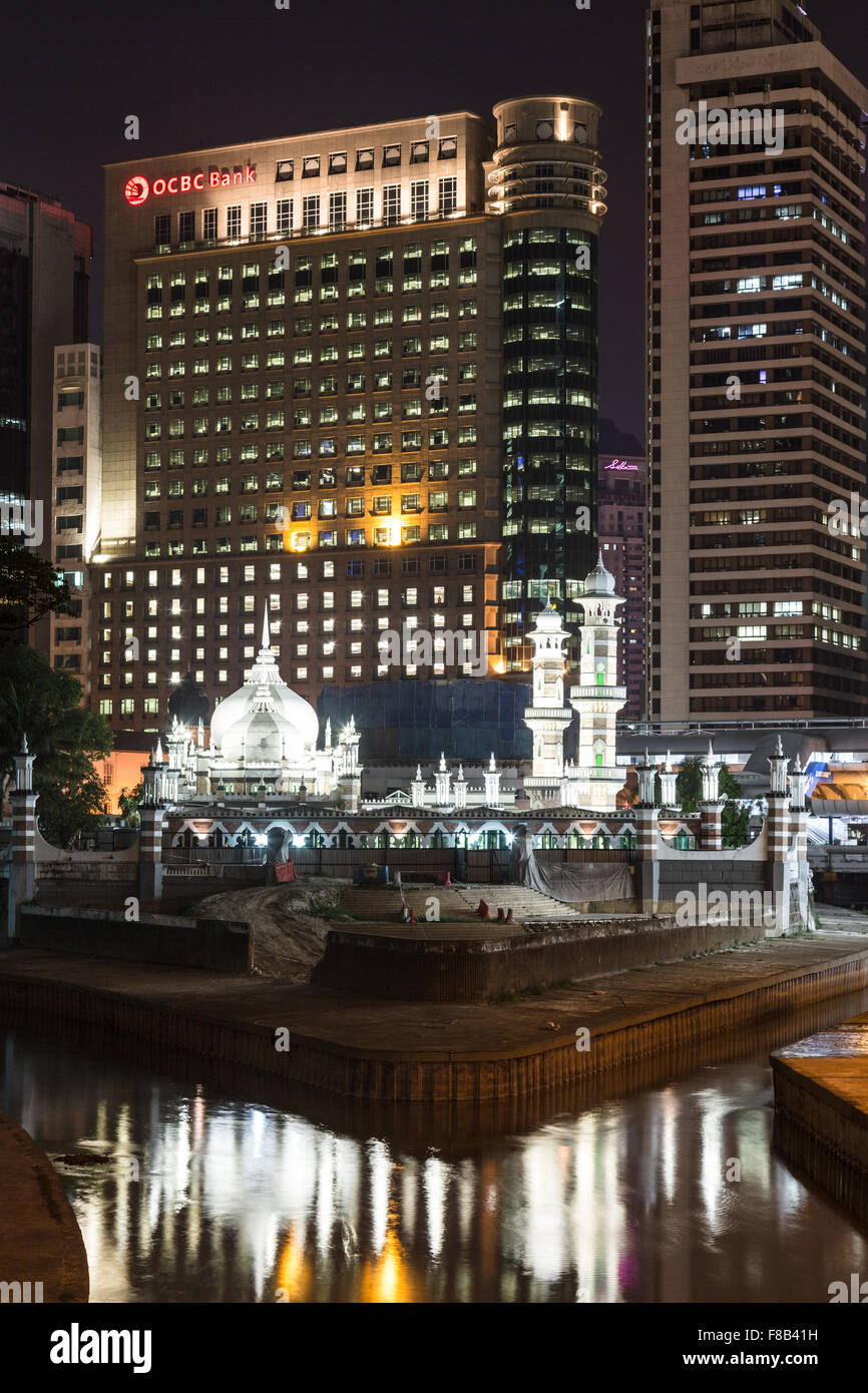A night view of one of Kuala Lumpur oldest mosque, Masjid Jamek, and bank buildings in the heart of Malaysia capital - Stock Image