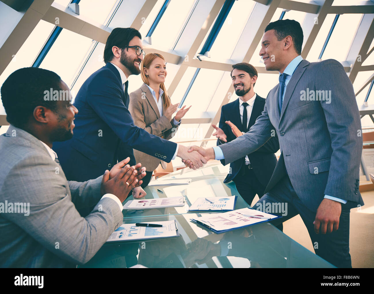 Business partners handshaking after signing contract - Stock Image