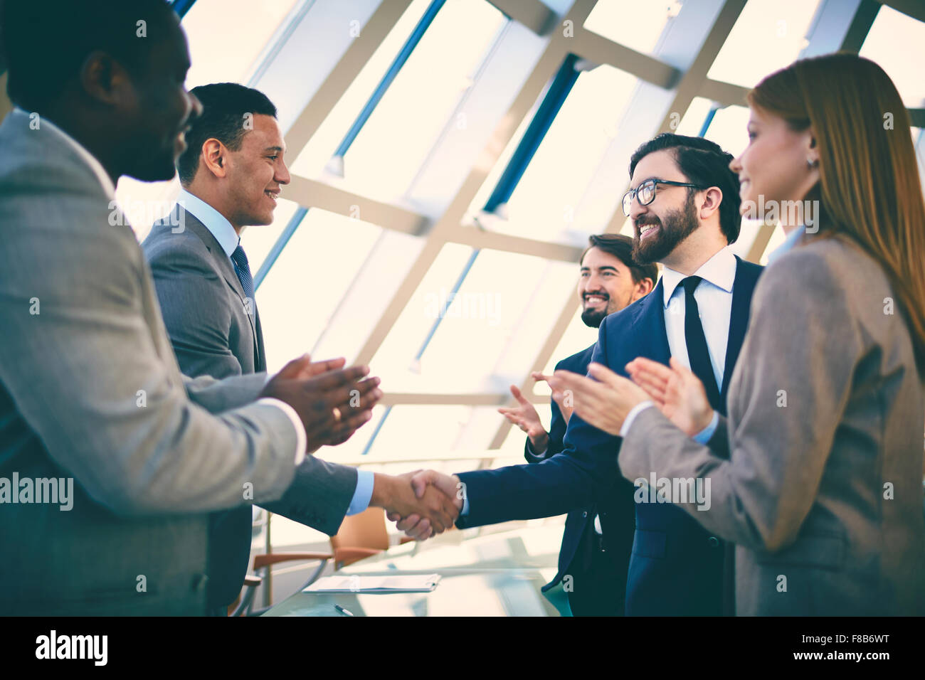 Business partners greeting each other after signing contract - Stock Image