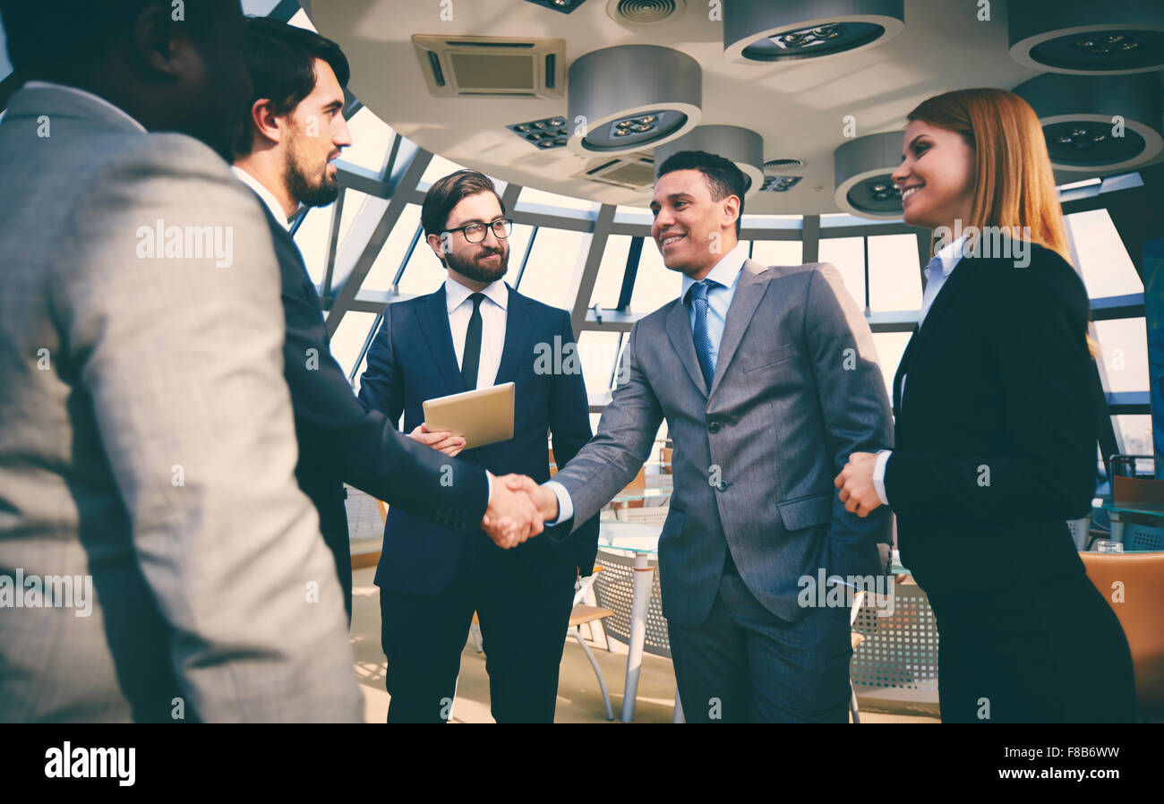 Business partners greeting one another by handshaking - Stock Image