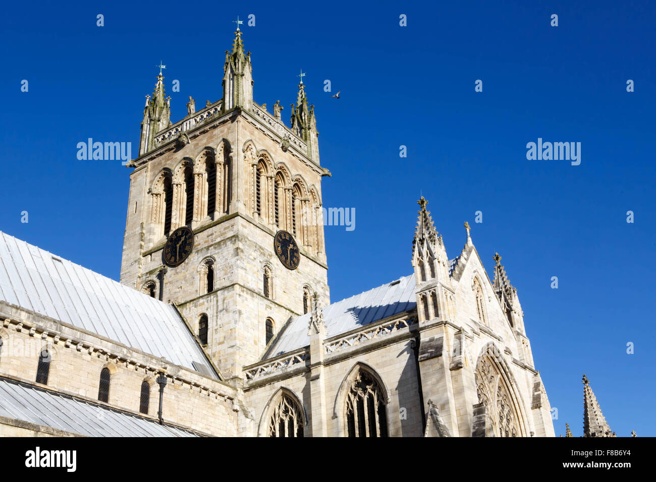 The south side of  Selby Abbey showing the tower against a clear blue sky background - Stock Image