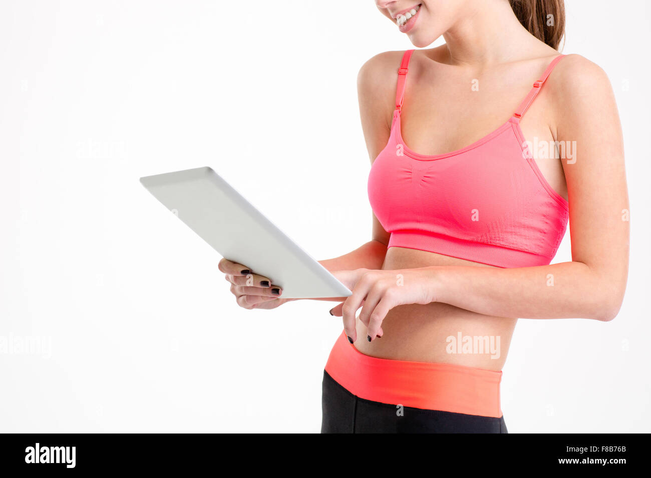 Closeup of tablet used by slim beautiful young sportswoman in tracksuit isolated over white background - Stock Image