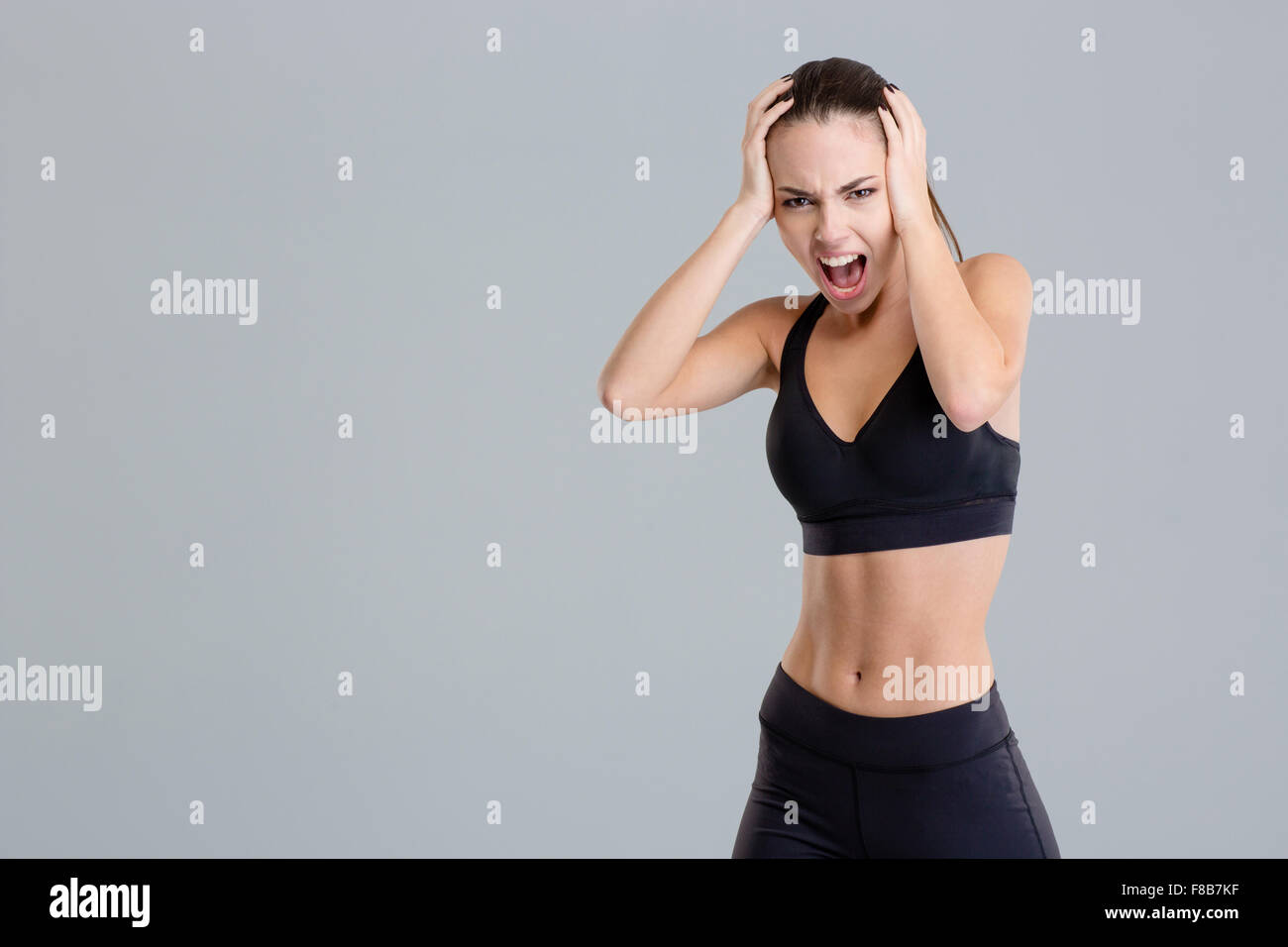 Crazy hysterical shouting fitness girl in black top and leggings isolated over grey background - Stock Image