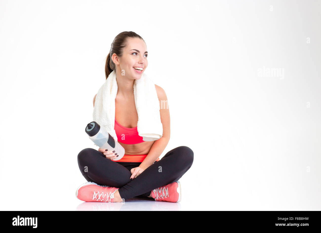 Happy beautiful young sportswoman with towel on her neck and bottle of water relaxing after training over white Stock Photo