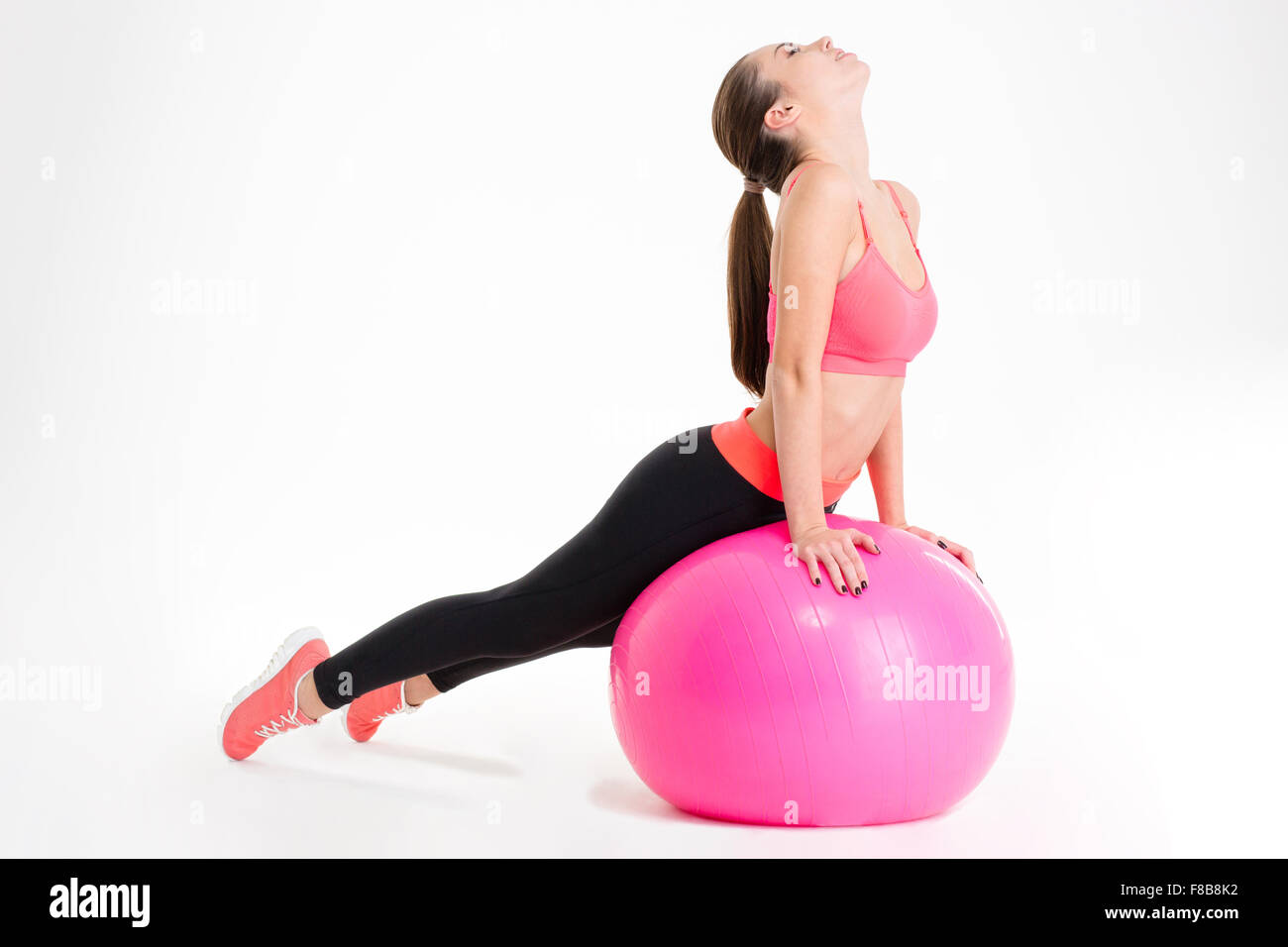 Focused attractive young fitness woman in pink top and black leggings doing stretching on pink fitball over white - Stock Image