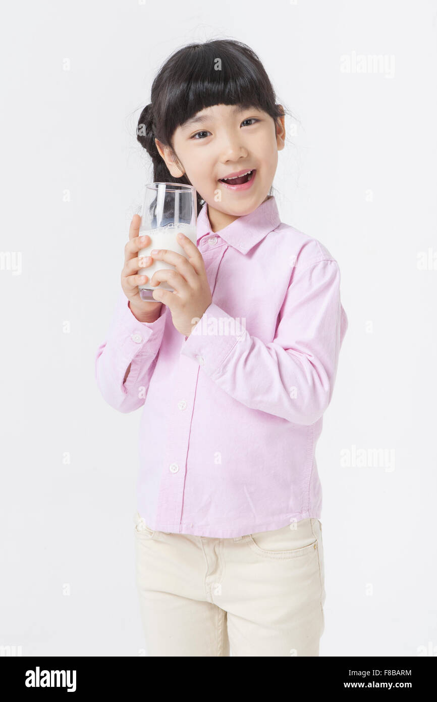 4004ee69375 Young Korean girl in pink shirt holding a glass of milk and smiling ...