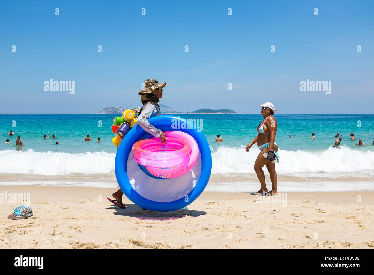 RIO DE JANEIRO, BRAZIL - MARCH 15, 2015: Beach vendor selling colorful beach toys carries his merchandise along - Stock Image