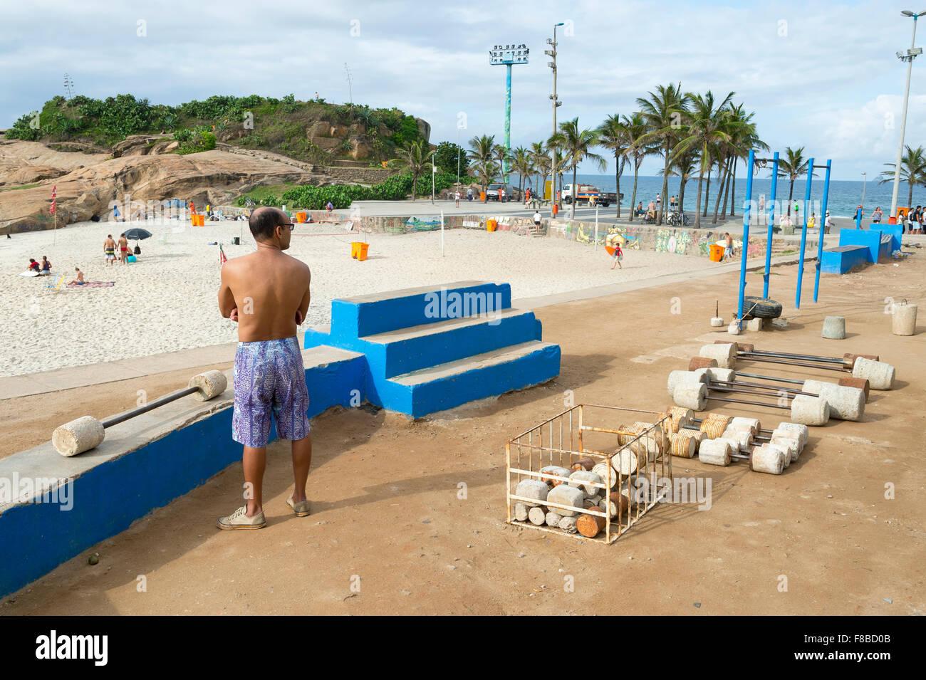 RIO DE JANEIRO, BRAZIL - FEBRUARY 12, 2015: Brazilian man exercises at an outdoor workout station at Arpoador near - Stock Image