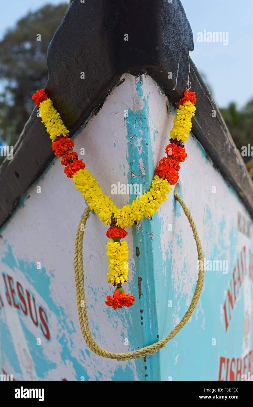 Flower garland on prow of fishing boat Colva Beach Goa India - Stock Image