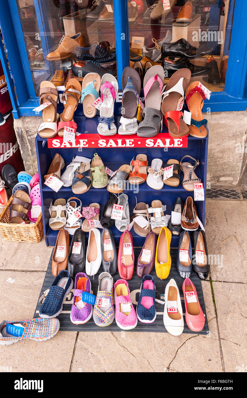 Shoes for sale on a shoe rack outside a Uk shop store - Stock Image