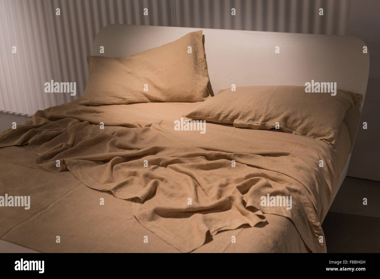 Luxury bed with crumpled  sheets and a warm blanket - Stock Image
