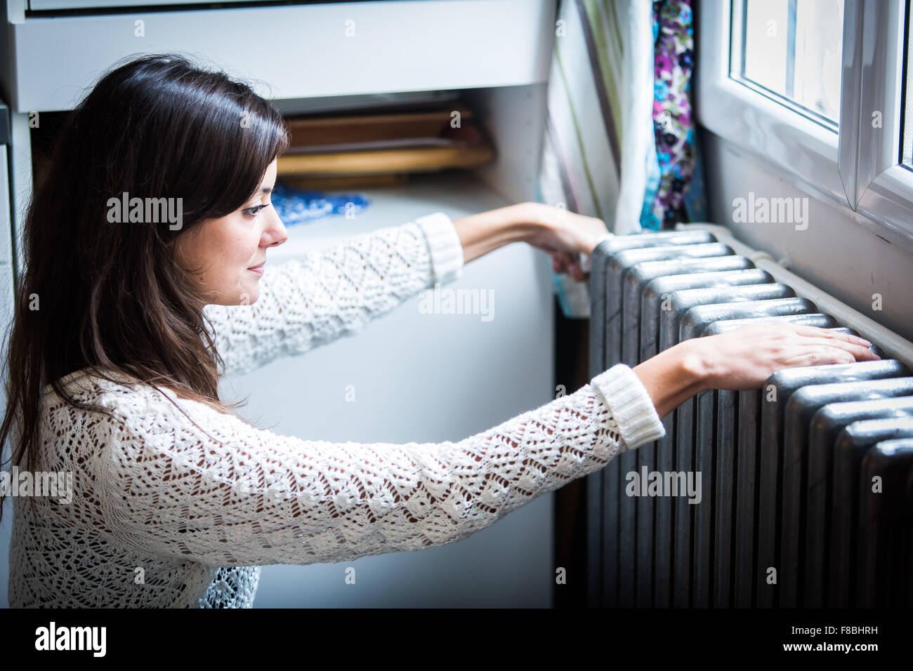 Woman adjusting a thermostatic radiator valve on a domestic radiator. - Stock Image