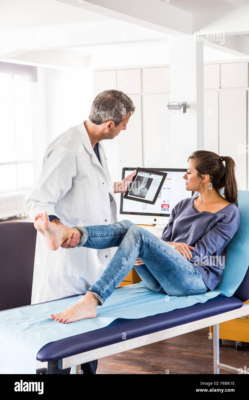 Doctor examining the ankle of a female patient. - Stock Image