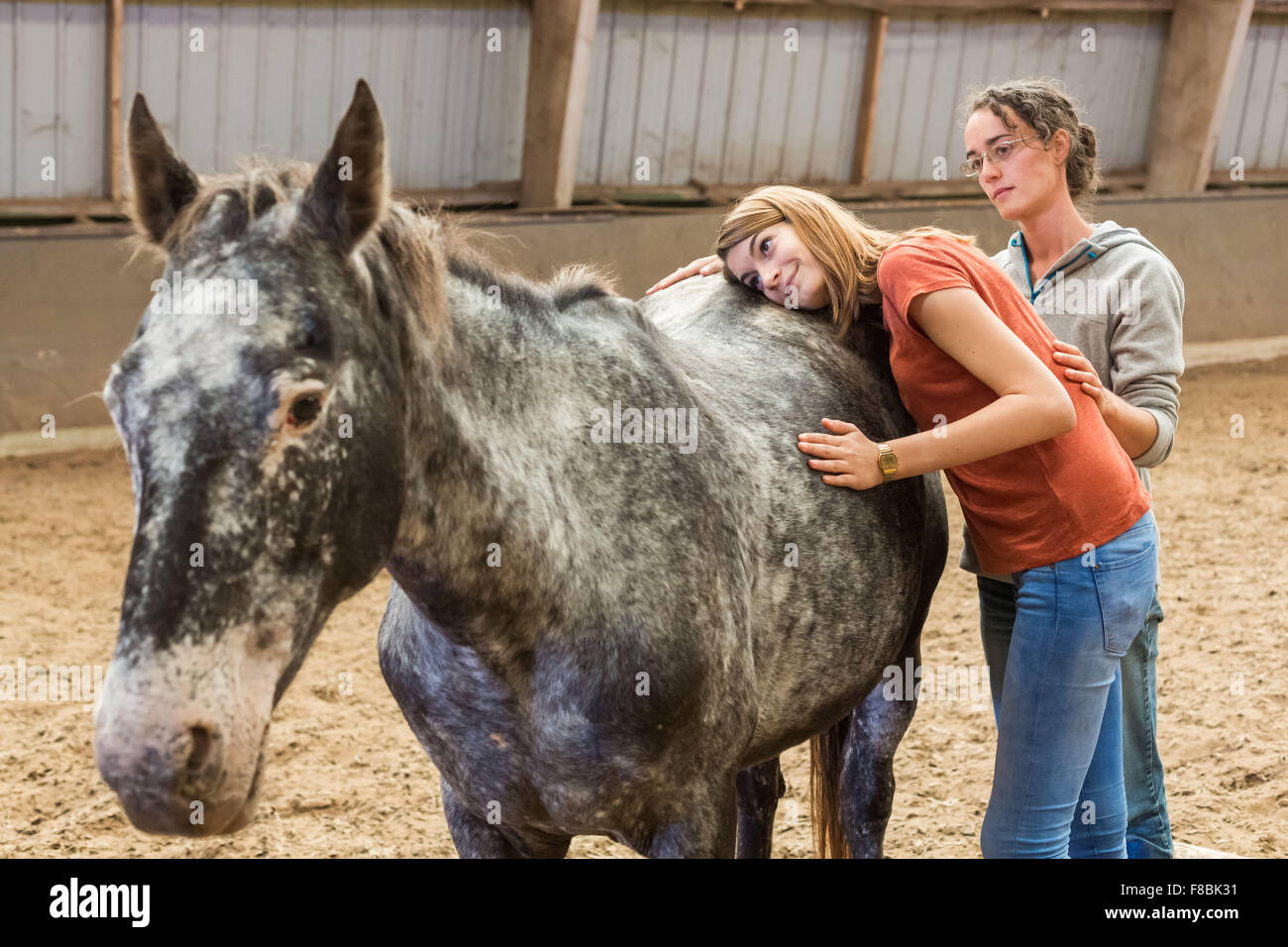 Young woman in horse therapy session with a therapist, Brie en Charente horseback riding, France. - Stock Image