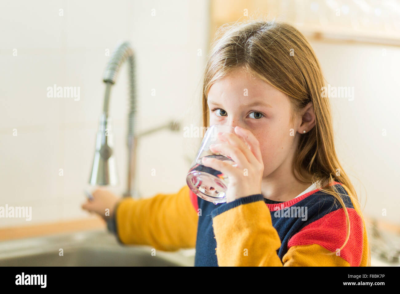 9-year-old girl drinking tap water. - Stock Image