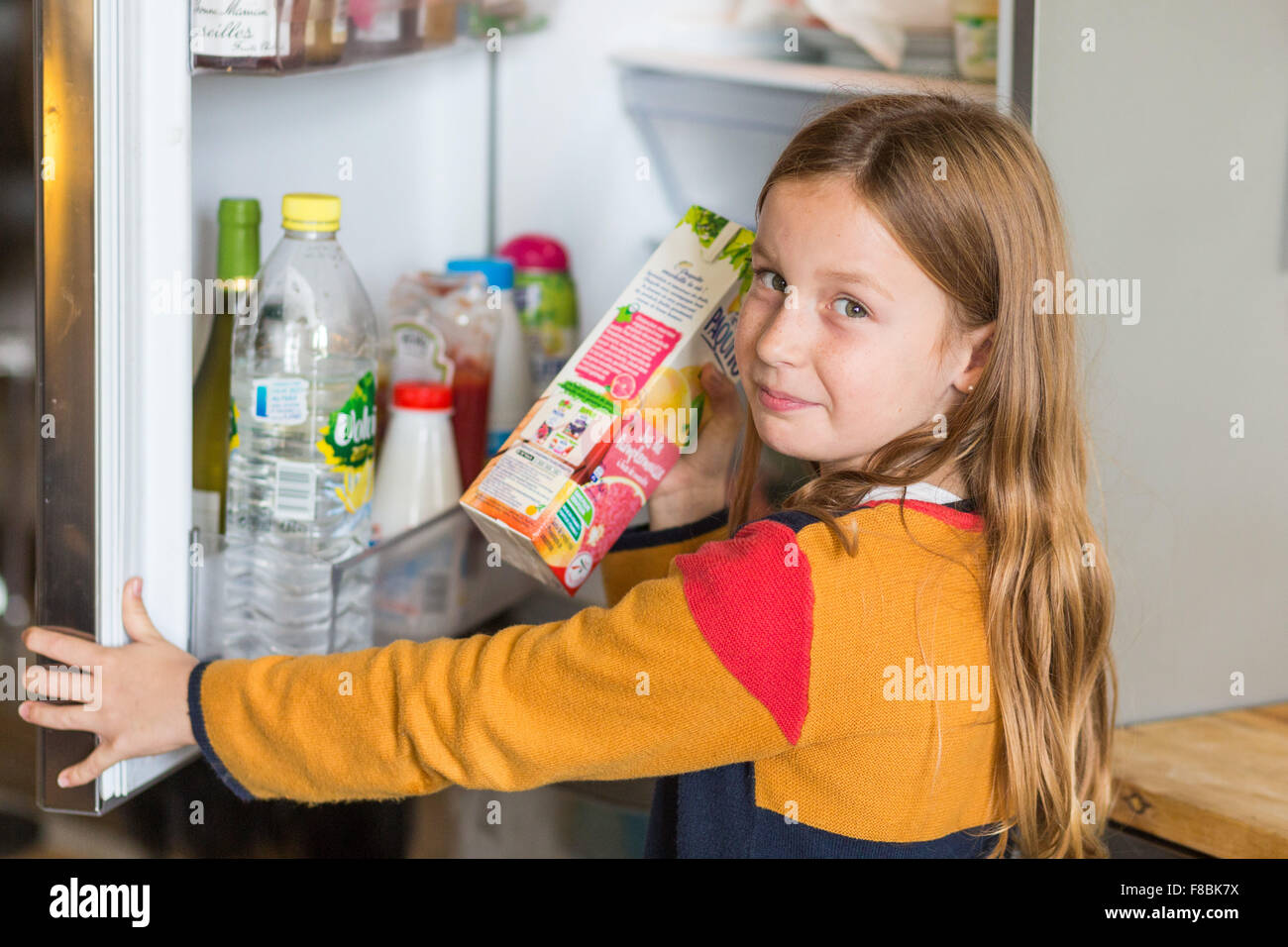 8 year old boy in front of a fridge. - Stock Image