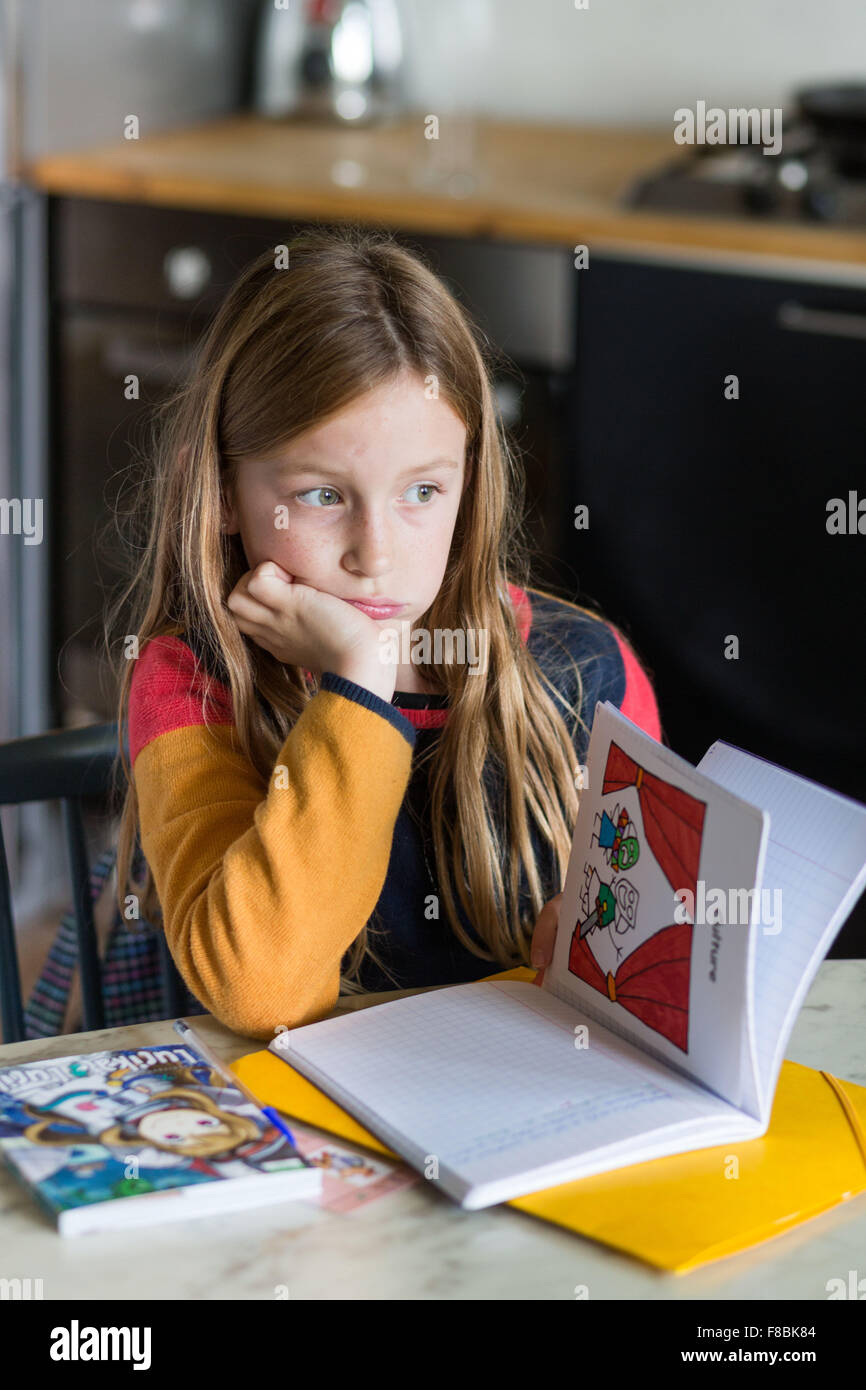 9-year-old girl doing her homework. - Stock Image