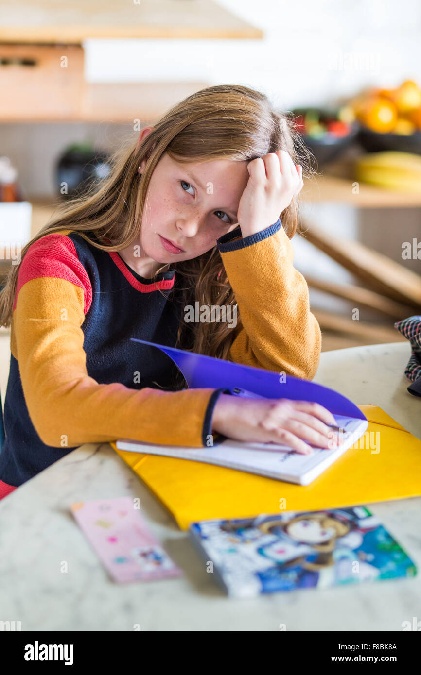 9-year-old girl doing her homework. - Stock Image