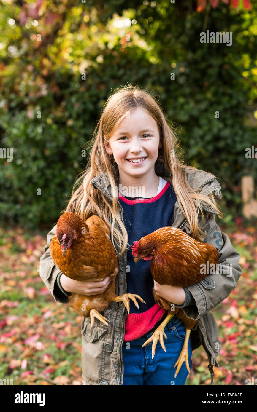 9-year-old girl with hens. - Stock Image