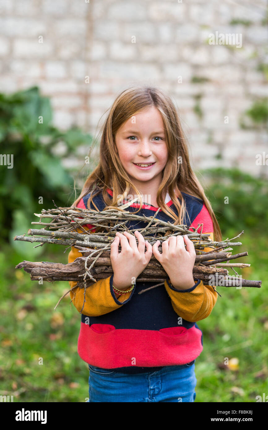 9-year-old girl collecting firewood. - Stock Image