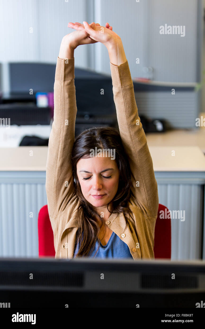 Office woman stretching arms at work. - Stock Image