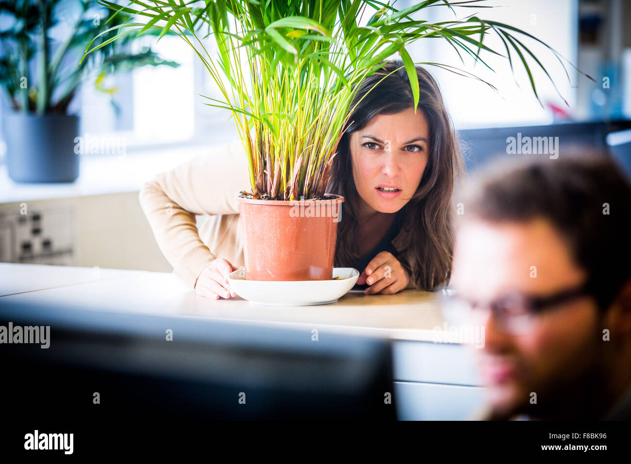 Woman watching his colleague in the office. - Stock Image