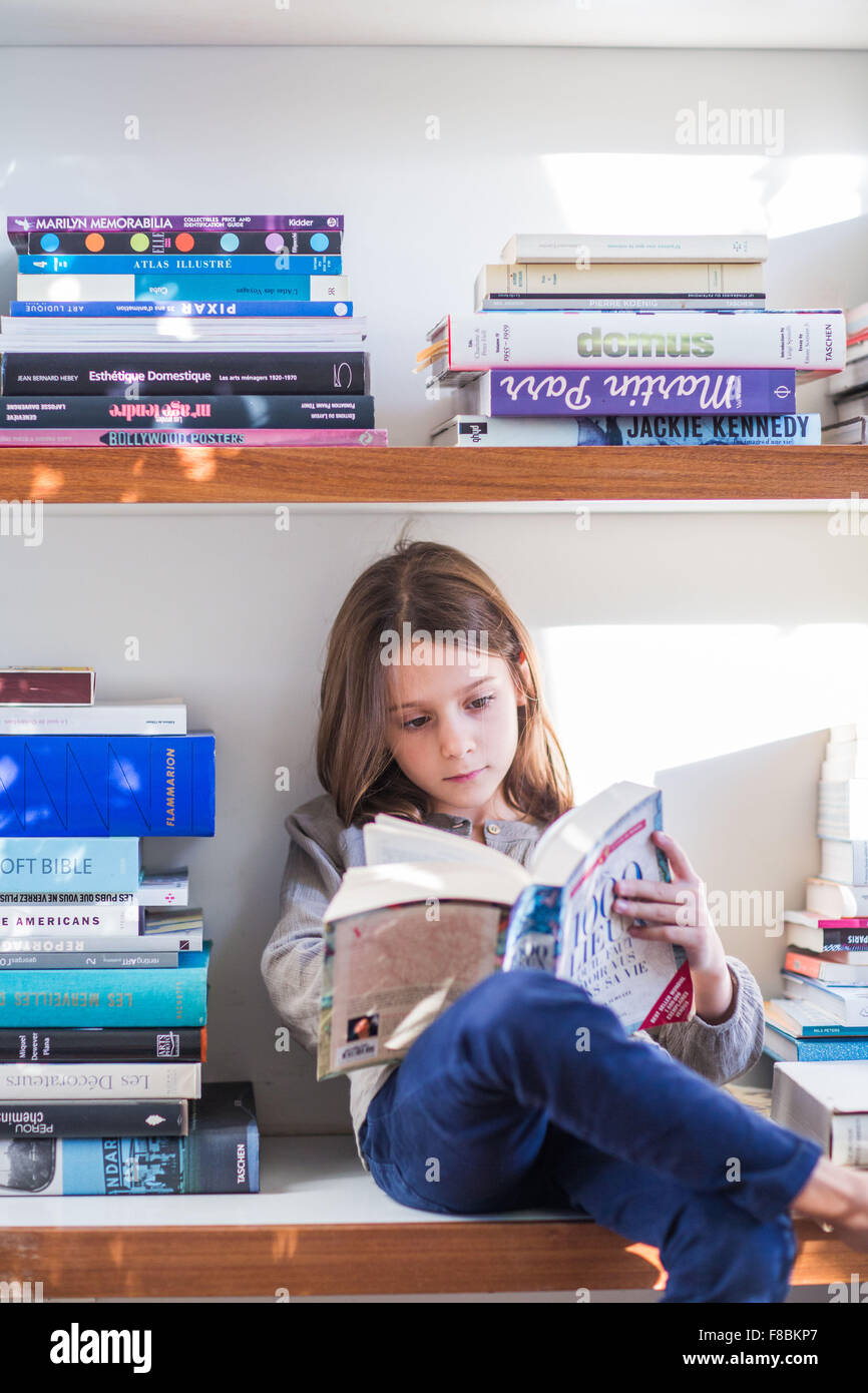 8 year-old girl reading. - Stock Image